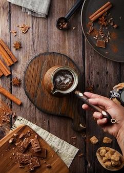 Flacher kakao auf eine rustikale oberfläche legen. türk mit holzgriff aus kakaoschokolade mit heißem getränk auf einem holztisch, gemütliche oberfläche, schokolade und zimt, festliches café, draufsicht von oben