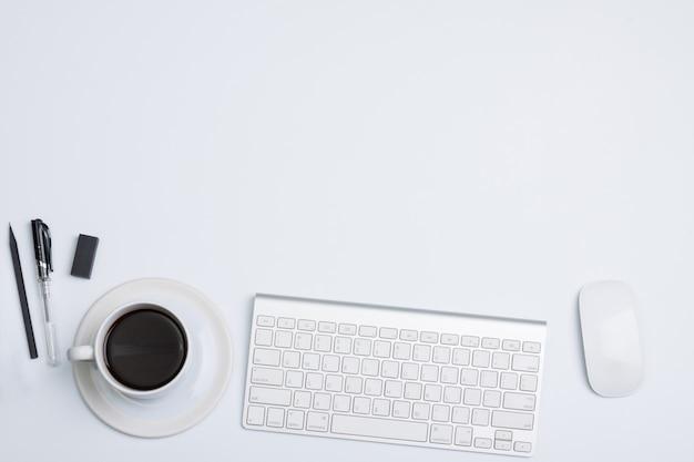 Flacher lage, moderner bürotischschreibtisch der draufsicht. weiße tasse kaffee, stift und maus tastatur