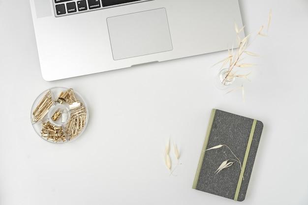 Flacher lageblogger- oder -freiberuflerarbeitsplatz mit einer tastatur und einem leeren notizbuch auf weiß