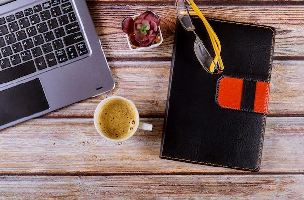 Flacher lagebürotisch-schreibtischarbeitsplatz mit laptoptastatur, notizbuch, gläsern und kaffeetasse