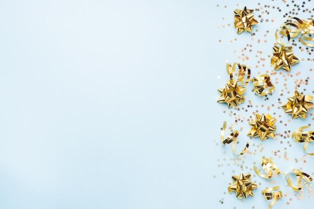 Flacher lagehintergrund für feier weihnachten und neues jahr. gold bänder bögen und konfetti sterne auf blauem grund. draufsichtkopienraum.