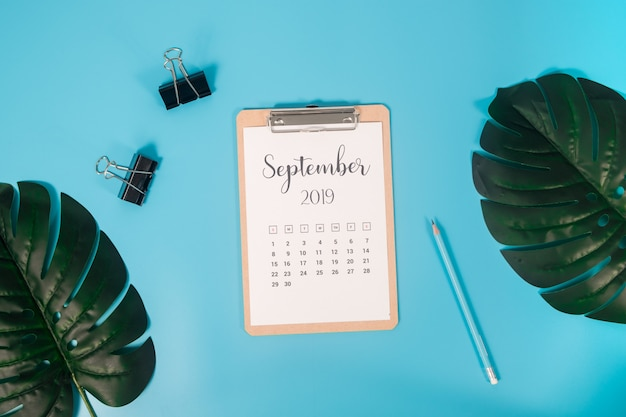 Flacher lagekalender mit klemmbrett, palmblättern und bleistift auf blauem hintergrund