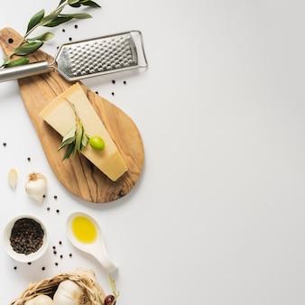 Flacher lageparmesankäse auf schneidebrett mit kopienraum