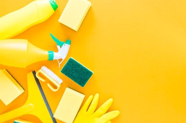 Flacher lagerahmen mit gelben reinigungsprodukten und -hintergrund