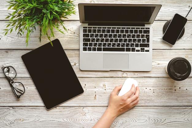 Flacher lageschreibtisch arbeitsplatz mit der weiblichen hand, draufsicht des laptops