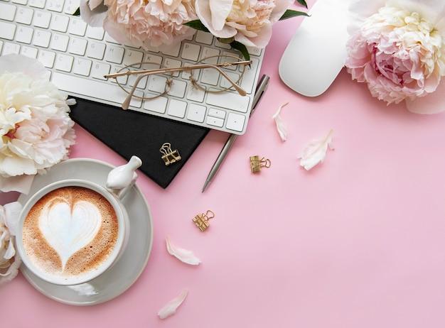 Flacher laien-draufsicht-frauenschreibtisch mit blumen. weiblicher arbeitsbereich mit laptop, blumenpfingstrosen, zubehör, notizbuch, gläser, tasse kaffee auf rosa hintergrund. urlaubshintergrund. kopierraum