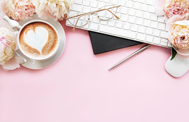 Flacher laien draufsicht frauenschreibtisch mit blumen. weiblicher arbeitsbereich mit laptop, blumenpfingstrosen, zubehör, notizbuch, gläser, tasse kaffee auf rosa hintergrund.