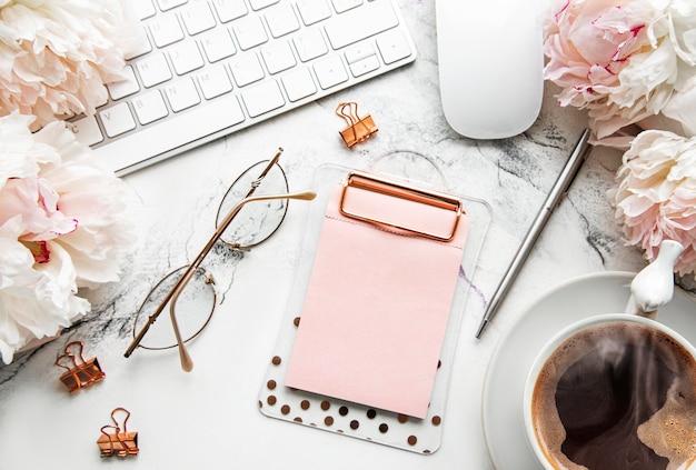 Flacher laien draufsicht frauenschreibtisch mit blumen. weiblicher arbeitsbereich mit laptop, blumenpfingstrosen, zubehör, notizbuch, gläsern, tasse kaffee auf weißem tisch. feiertagstisch. kopierraum