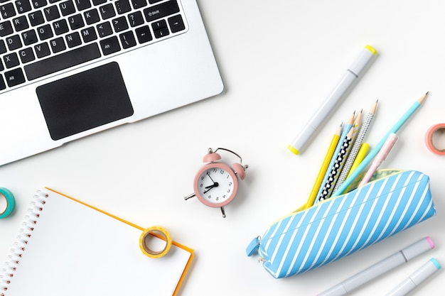 Flacher laien-draufsicht-laptop, federmäppchen und briefpapier auf weißem tisch