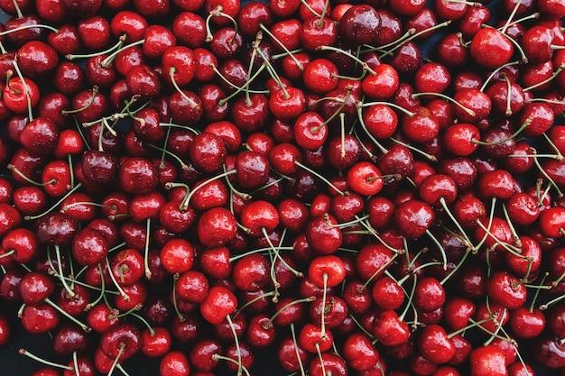 Flacher laienhintergrund mit haufen frischer roter süßkirsche. ökologischer anbau von nahrungsmitteln auf dem bauernhof. gesunde ernährung lifestyle-konzept. foto in hoher qualität