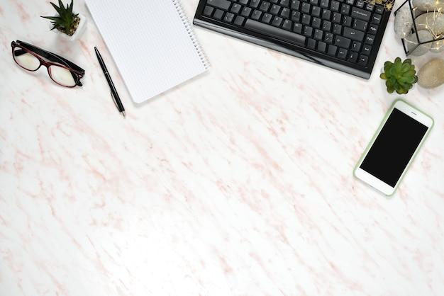 Flacher laienmarmorschreibtisch mit telefon, tastatur und notizbuch