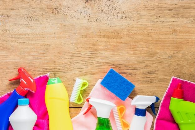 Flacher laienrahmen mit reinigungsprodukten und hölzernem hintergrund