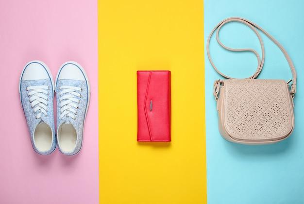 Flacher laienstil auf modischen turnschuhen mit farbigem hintergrund, rote lederbrieftasche, tasche mit riemen.
