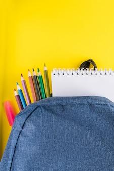 Flacher laienstudentenrucksack und büromaterial auf gelbem hintergrund.