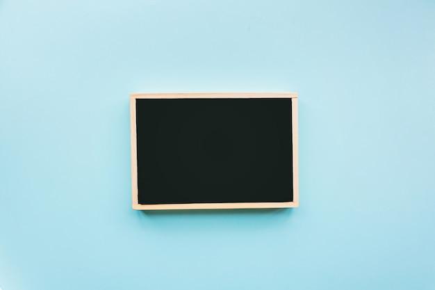 Flacher lat des schwarzen kreidebrettes auf hintergrund des blauen papiers