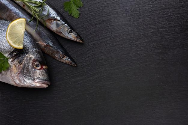 Flacher lat frischer fisch und zitrone auf tabelle