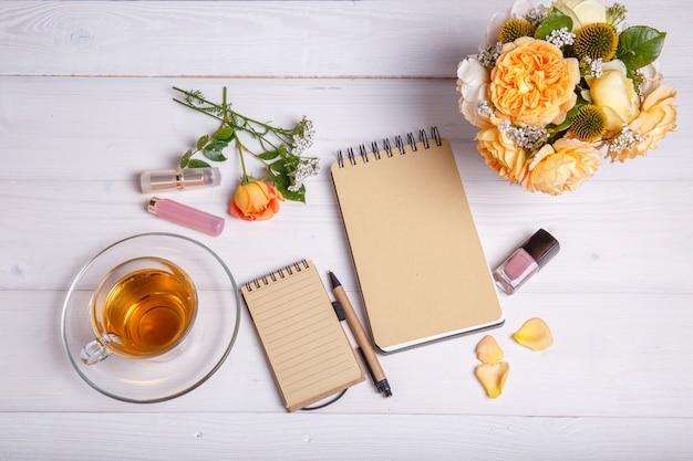 Flacher lay-schreibtisch mit tee, kosmetik und einem strauß englischer rosen