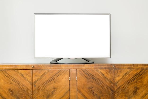 Flacher lcd-fernseher auf braunem holzschrank im wohnzimmer mit weißem bildschirm