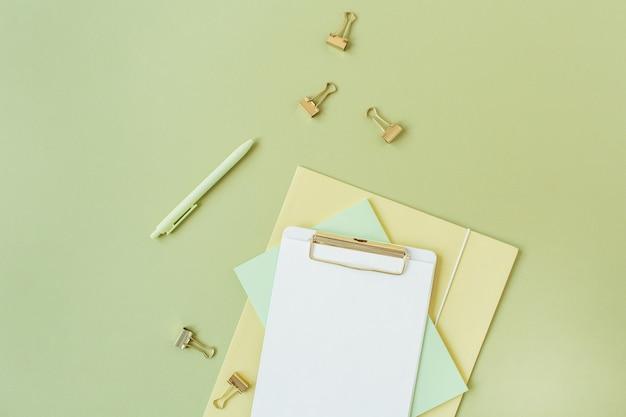 Flacher minimalistischer home-office-schreibtisch mit leerem blatt zwischenablage mit kopierraum für text, stift, clips auf grün