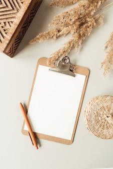 Flacher minimalistischer home-office-schreibtisch mit leerer zwischenablage mit kopierraum für text, schilfzweig, sarg auf neutral