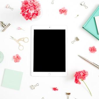 Flacher mode-schreibtisch. weiblicher arbeitsplatz mit tablette des leeren bildschirms, rote blumen, zubehör, tadelloses tagebuch auf weißem hintergrund spott oben. ansicht von oben