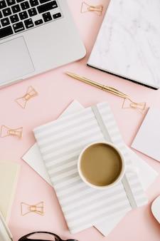 Flacher, moderner weiblicher arbeitsbereich mit laptop und schreibwaren auf pastellrosa