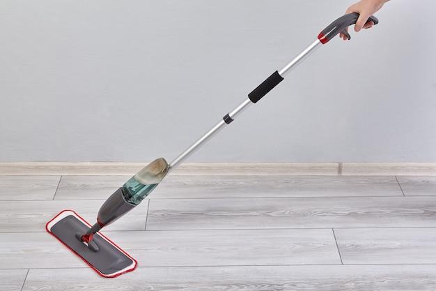 Flacher mopp mit spray und mikrofaserkopf reinigt den laminatboden im raum von staub und schmutz.