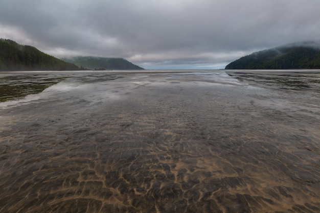 Flacher offener strand mit sand und keine menschen mit distanzwolke, sieht entspannender ort auf vancouver island, british columbia, kanada.