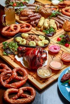 Flacher oktoberfest-esstisch mit gegrillten fleischwürsten, brezelgebäck, kartoffeln, gurkensalat, saucen, bieren