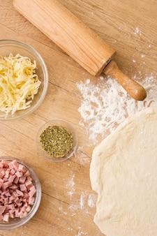 Flacher pizzateig mit tomatensauce-mozzarella-schinken und nudelholz