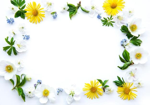 Flacher rahmen mit frühlingsblumen, blättern und blütenblättern lokalisiert auf weißem tisch. draufsicht