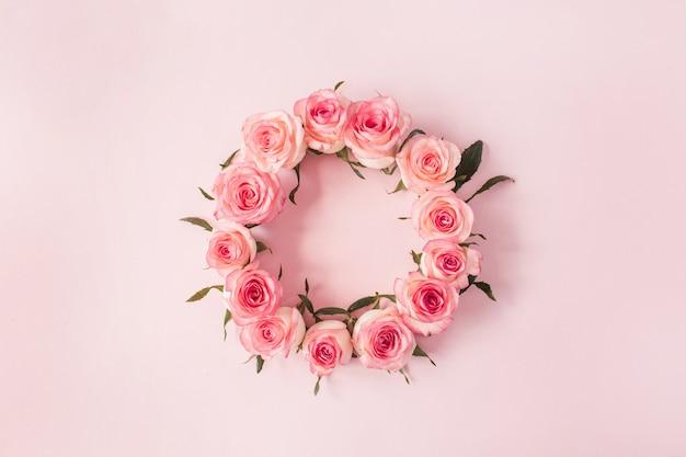 Flacher rahmenrahmen mit leerem kopierraummodell aus rosa rosenblütenknospen auf rosa oberfläche