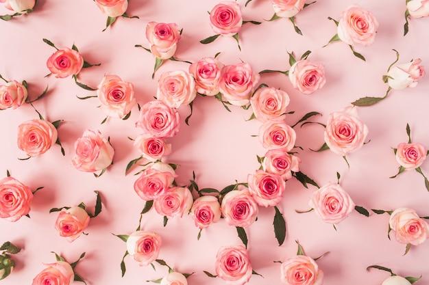 Flacher rahmenrahmen mit leerem kopierraummodell aus rosa rosenblütenknospen auf rosa