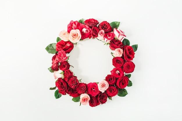 Flacher rahmenrahmen mit leerem kopierraummodell aus rosa und roten rosenblüten auf weiß