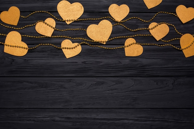 Flacher rand aus goldenen herzen und perlen. festliches dekor auf einem schwarzen hölzernen hintergrund. von oben betrachten.