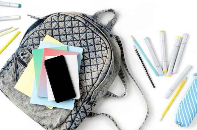 Flacher rucksack mit draufsicht und verschiedenem buntem briefpapier