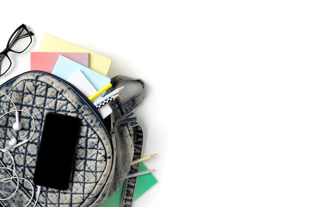 Flacher rucksack mit draufsicht und verschiedenen bunten schreibwaren auf weißem tisch. zurück zum schulkonzept