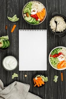 Flacher salat mit couscous und leerem notizbuch