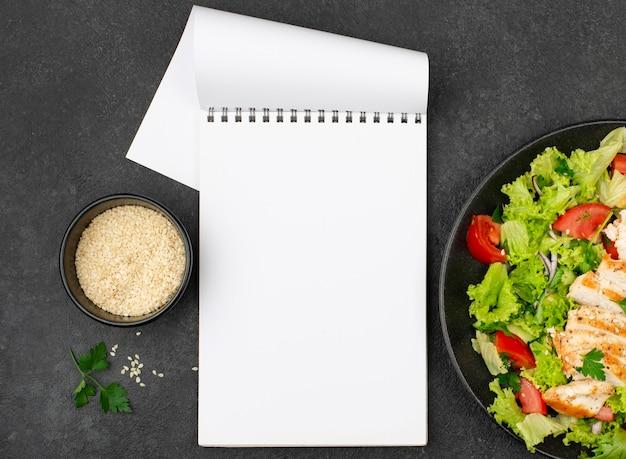 Flacher salat mit hühnchen und sesam mit leerem notizblock