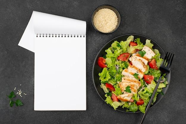 Flacher salat mit hühnchen und sesam mit leerem notizbuch