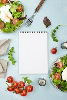 Flacher salat mit spiegelei und tomaten mit leerem notizbuch
