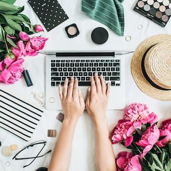 Flacher schreibtisch im stil mit laptop, rosa pfingstrosenblüten, kosmetik, accessoires. frau arbeitet am computer