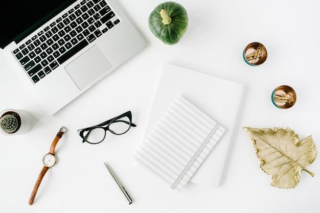 Flacher schreibtisch mit draufsicht. arbeitsbereich mit laptop, kürbis, brille, uhr, tagebuch, stift und kaktus auf weiß.