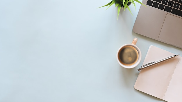 Flacher schreibtisch mit draufsicht. arbeitsbereich mit rohling, laptop, büromaterial, stift, grünem blatt und kaffeetasse auf blau