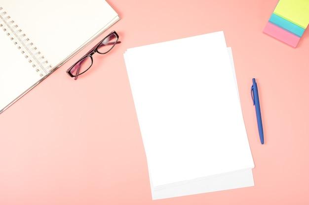 Flacher schreibtisch mit draufsicht. leeres papier, brille, notizblock, notizpapier auf rosa tisch.