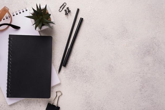 Flacher schreibtisch mit notizbüchern und gläsern
