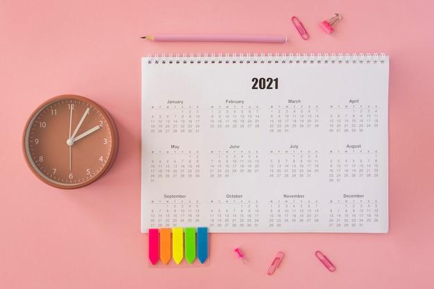 Flacher schreibtischkalender auf rosa hintergrund legen