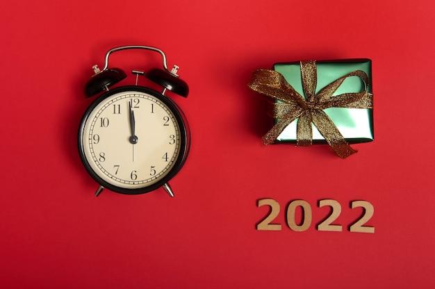 Flacher schwarzer wecker mit mitternacht auf dem zifferblatt, holzziffern als symbol für das jahr 2022 und ein weihnachtsgeschenk in glänzend grünem geschenkpapier mit goldenem band und schleife. platz kopieren