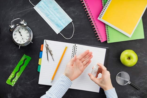 Flacher student mit desinfektionsmittel über dem schreibtisch