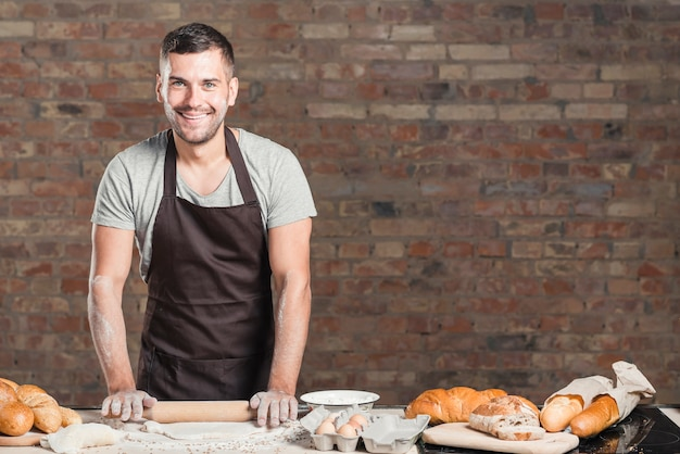 Flacher teig des lächelnden bäckers mit nudelholz auf küche worktop